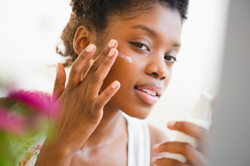 black-woman-putting-on-skin-care-lotion