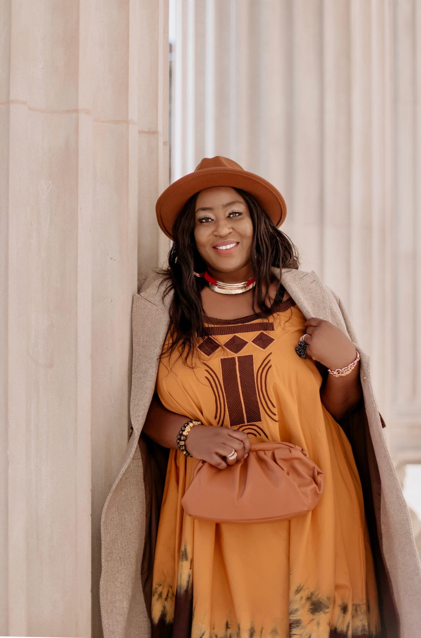 beautiful-black-woman-maxi-dress-beige-coat-fedora-hat-edwige-amaizo-foltek